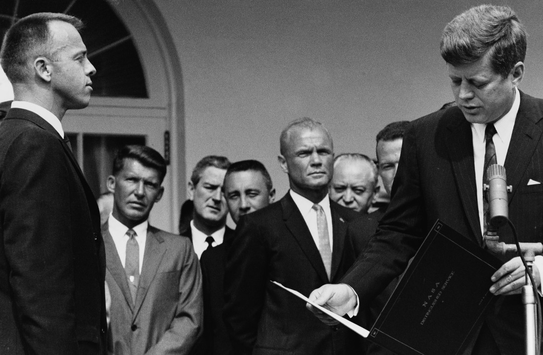 1961, White House, Washington, D.C., USA --- President John F. Kennedy awards astronaut Alan Shepard, the NASA Distinguished Service Medal for his first American manned space flight on the Mercury mission, at the White House. Behind them stand other astronauts including Wally Schira, Gus Grissom, and John Glenn. --- Image by © Dean Conger/CORBIS